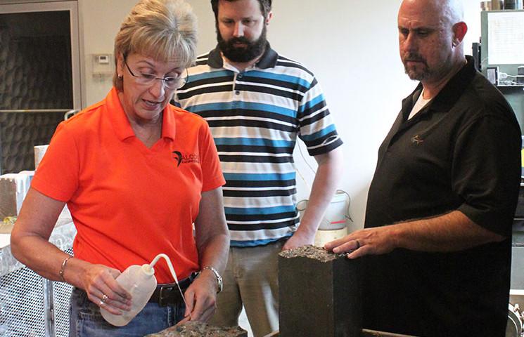 Falcon President Margaret Robertson trains staff on flexural testing of concrete beam specimens.